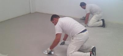Dos personas llevando a cabo la aplicación del microcemento en suelo.
